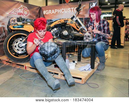 St. Petersburg Russia - 15 April, Application of airbrushing to motor accessories,15 April, 2017. International Motor Show IMIS-2017 in Expoforurum. Visitors and participants of the annual moto-salon in St. Petersburg.