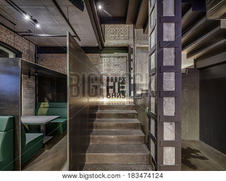 Hall in a cafe in a loft style with brick and concrete walls, column, stairway with reticulated partition and glowing lamps. There are green sofas with a gray table and partitions, signboard on wall.