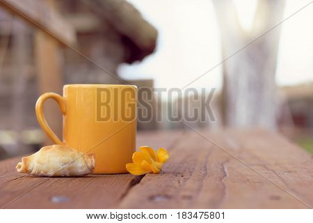 Croissant with a yellow mug and flower on a table on a background of a rural landscape/ hot drink and dessert in the fresh air