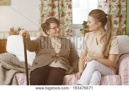 Caregiver And Woman Sitting On A Sofa