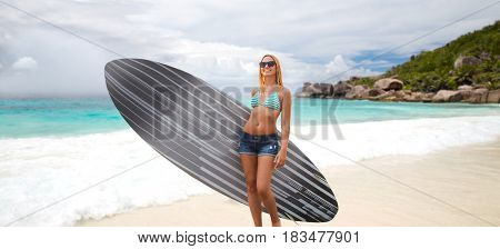 summer vacation, water sport and people concept - smiling young woman with surfboard over exotic tropical beach and ocean background