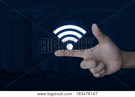 Wifi icon on finger over world map and modern city tower Technology and internet concept Elements of this image furnished by NASA