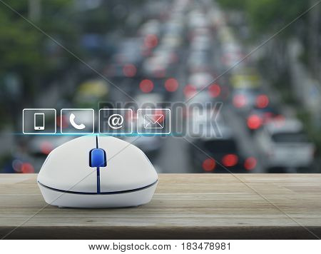 Telephone mobile phone at and email buttons with wireless computer mouse on wooden table over blur of rush hour with cars and road Customer support concept
