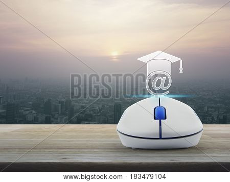 Wireless computer mouse with e-learning icon on wooden table over modern city tower at sunset vintage style Study online concept