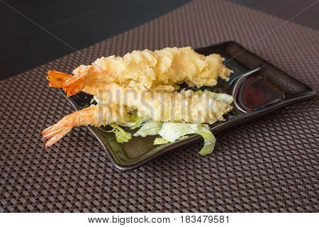 Japanese CuisineTempura Shrimps (Deep Fried Shrimps) with sauce and vegetables on a black plate. Brown backgroundshallow depth of field