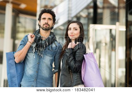 Couple doing shopping in a urban street. Shallow depth of field, focus on the woman
