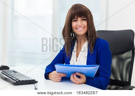 Young secretary at her desk in a modern office