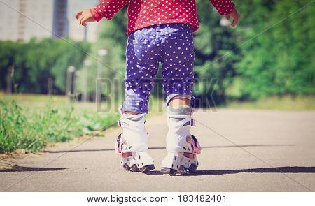 little girl learning roller skating outdoors, kids sport