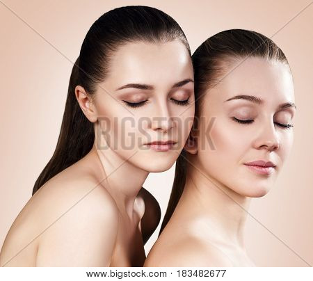Two beautiful sensual young women with closed eyes. Over beige background.
