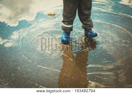 little boy in rain boots play in puddle, kids ourtdoor activities