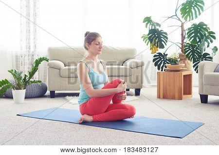 Wide shot of young sportswoman doing yoga fish pose on yoga mat