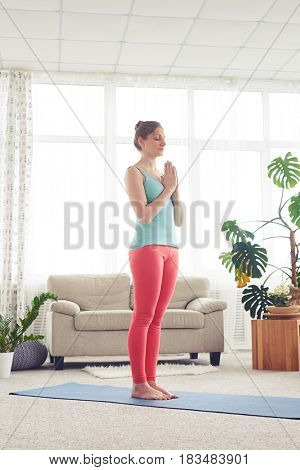 Side view of pretty woman meditating on yoga mat indoor. Wearing comfortable sport clothes