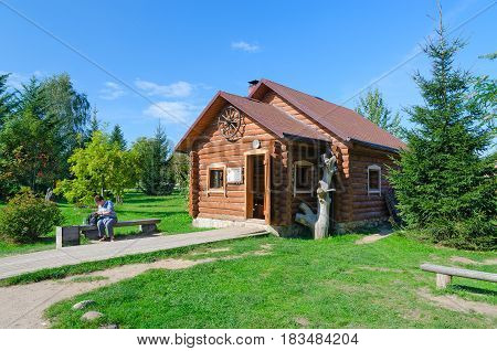 DUDUTKI BELARUS - SEPTEMBER 6 2014: Unknown woman is near woodworking workshop of museum of ancient folk crafts and technologies in Minsk region Belarus