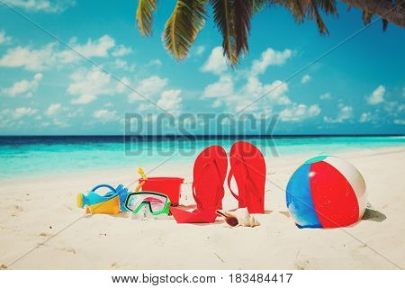 Colored slippers, toys and diving mask at tropical beach