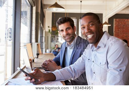 Portrait Of Businessmen Meeting In Coffee Shop