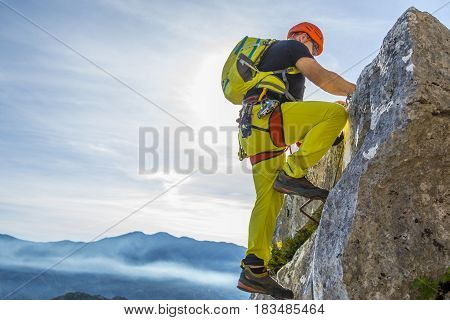 Male alpinist in special outfit climbing rock on background of summit and sky