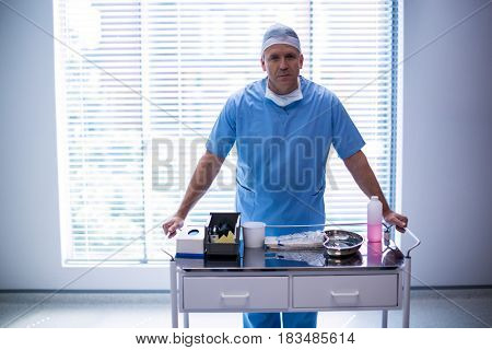 Portrait of male surgeon holding trolley at hospital