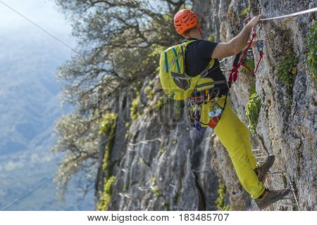 Male climber in special outfit climbing cliff with mountaineering equipment