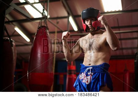 Confident boxer performing boxing stance in fitness studio