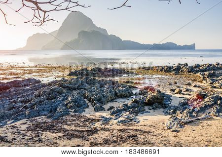 Rocky Beach during low tide in morning light in front of amazing Cadlao Island, El-Nido, Palawan, Philippines.