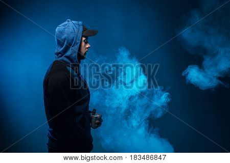 Vaping Man Holding A Mod. A Cloud Of Vapor.