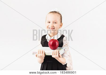 Book, School, Kid. Smiling Little Girl With Big Backpack Holding Books And Big Red Apple Against Whi