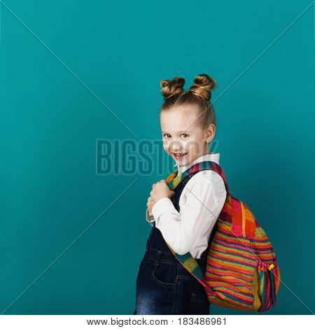 Beautiful Smiling Little Girl With Big Backpack Standing Against Blue Wall.