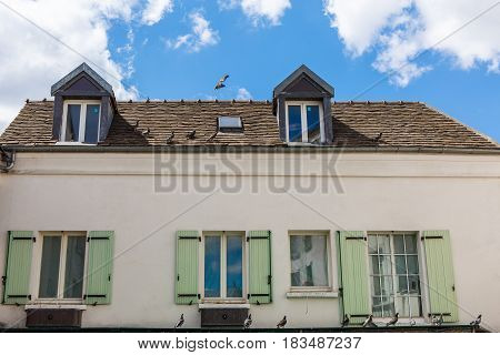 House in France with windows and green shutters