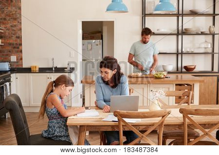 Mother Helps Daughter With Homework As Father Makes Meal