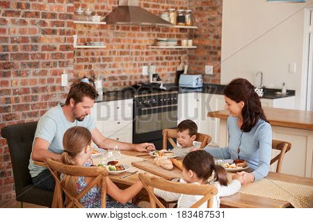 Family Praying Before Eating Meal In Kitchen Together