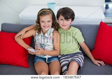 Portrait of sibling sitting on sofa with mobile phone in living room at home