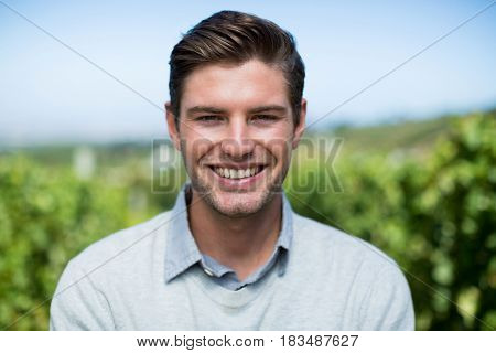 Portrait of smiling young man at vineyard against blue sky