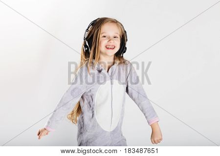 Adorable Little Girl In Headphones Enjoy With A Music.