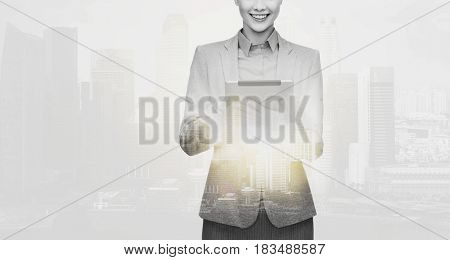 business, people and technology concept - smiling businesswoman with tablet pc computer over city buildings and double exposure effect