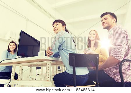 business, startup and people concept - happy creative team or students drinking coffee at office
