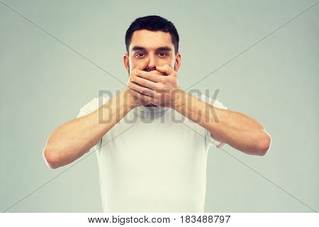 emotion, silence and people concept - man in white t-shirt covering his mouth with hands over gray background