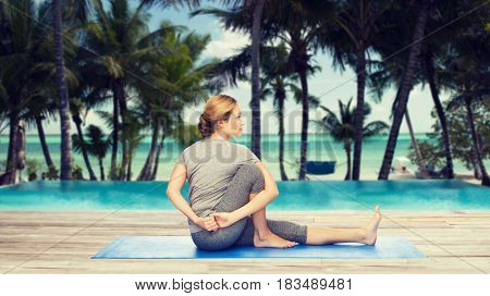 fitness, sport, people and healthy lifestyle concept - woman making yoga in twist pose on mat over hotel resort pool on tropical beach background