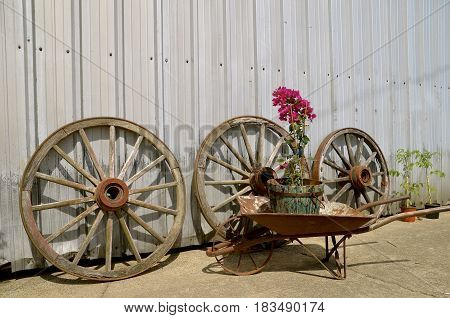 Old wooden wagon wheels, and rusty wheelbarrow lean against a metal corrugated side of a building.