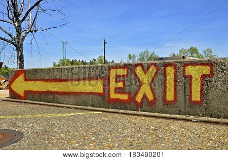 Brightly colored exit sign printed on a poured concrete wall or fence provides directions with an arrow