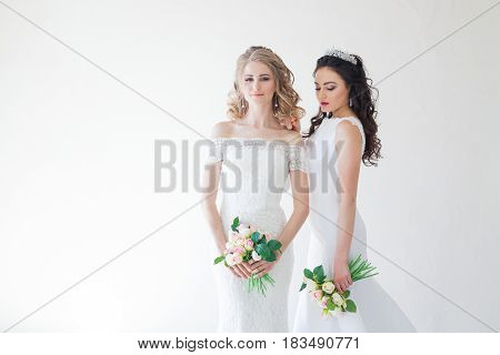 two wedding bride with a bouquet of flowers wedding hair blonde and brunette