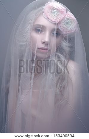 A young girl in the image of a bride with a veil on her face. Beautiful model with a wreath of flowers on her head. A gentle wedding image. Beauty of the face.