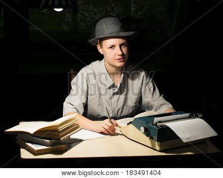 Portrait of a girl in a hat sitting at a table with a typewriter and books think about the idea at night