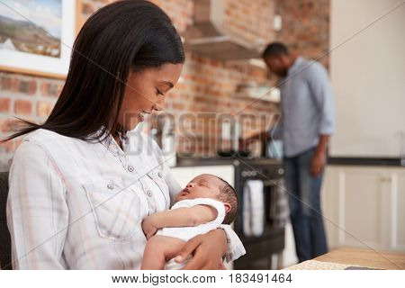 Mother On Laptop Holds Newborn Son As Father Makes Meal