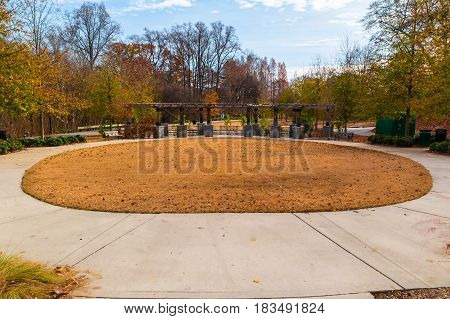 Oval lawn with dry grass and Leaders Grove Arbor in the Piedmont Park in sunny autumn day Atlanta USA