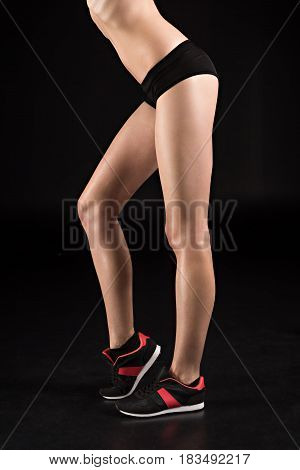 Low Section Of Sportswoman Legs In Sneakers Isolated On Black