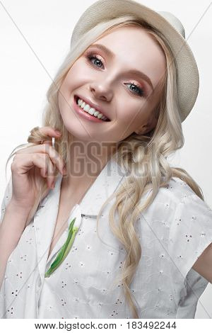 Young smiling girl with curls in a hat. A beautiful model in a white shirt and a brooch-flower. Gentle makeup. Summer light image. Beauty of the face.