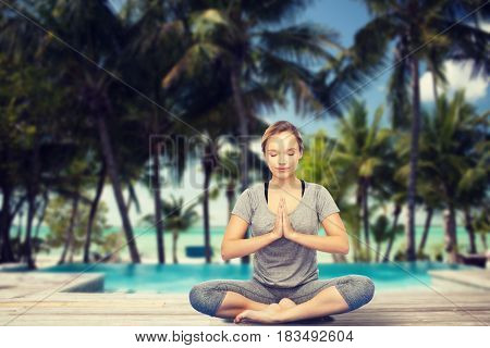 fitness, sport, people, resort and healthy lifestyle concept - woman making yoga meditation in lotus pose over swimming pool and tropical beach with palm trees background