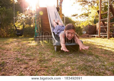 Portrait Of Girl Playing Outdoors At Home On Garden Slide