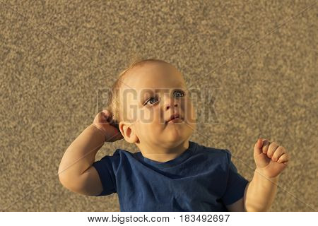 Thoughtful Infant Boy Sitting Against The Wall And Looking Away. Posing Toddler Boy With Unusual Sha