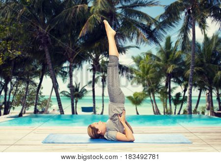 fitness, sport, people and healthy lifestyle concept - woman making yoga in shoulderstand pose on mat over hotel resort pool on tropical beach background